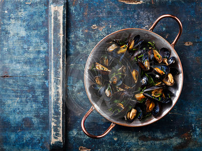 Mussels in copper cooking dish on blue background