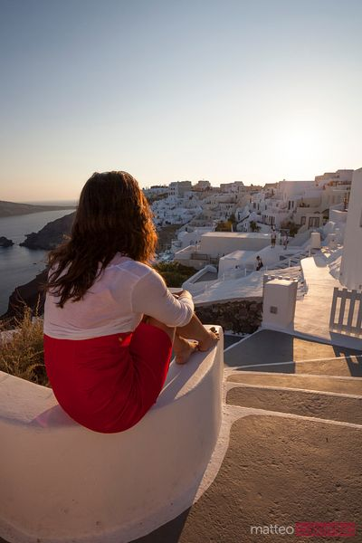 Woman watching sunset in the famous greek village of Oia, Santorini
