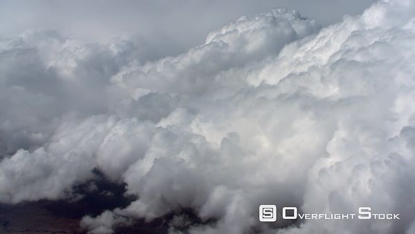 Climbing flight alongside cumulus clouds, passenger POV
