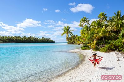 Tourist on idyllic tropical beach of One Foot Island, Aitutaki, Cook Islands