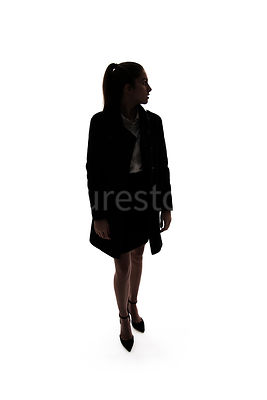 A woman, in silhouette, walking and looking away – shot from eye level.