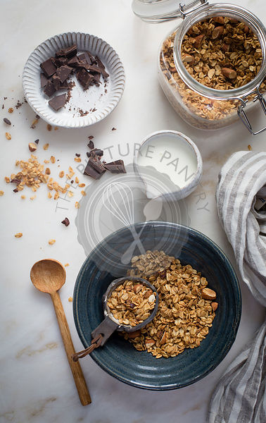 Peanut butter granola with cocoa nibs and chopped almonds and dark chocolate with milk on a marble table on top view
