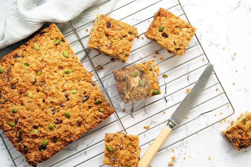 Apricot, pumpkin seed and oatmeal slice cut into pieces, cooling on a wire rack.