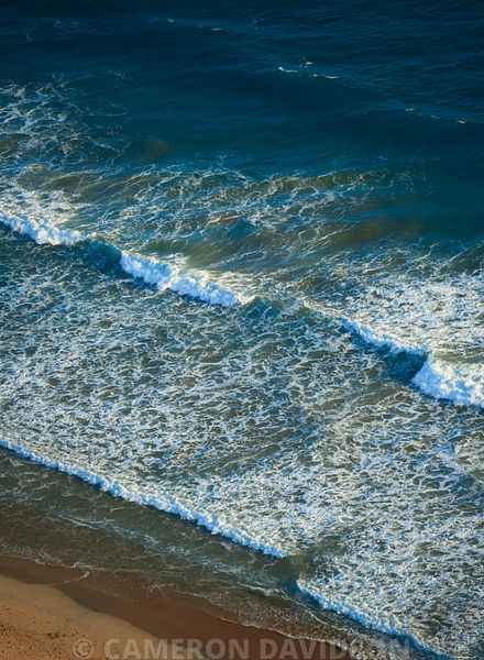 Aerial of surf breaking on the southern California coastline
