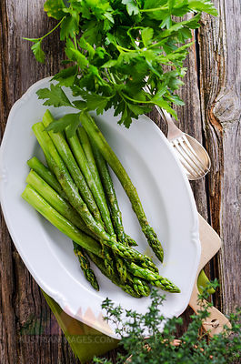 Plate of steamed green asparagus, Asparagus officinalis, and parsley on wood