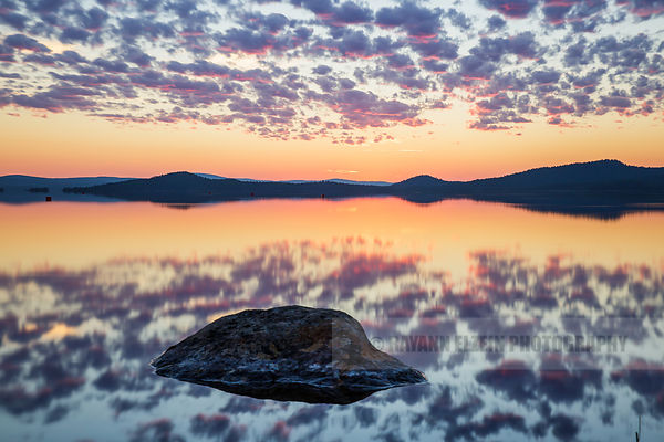 Perfect reflection of a surreal sky after the first sunset following the midnight sun period