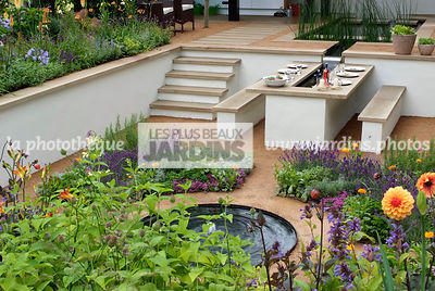Jardin contemporain en contre-bas. Meuble de jardin : table et banc. Terrasse. Escalier. Designer : Thomas Hoblyn Design Agency. Hampton Court. Angleterre