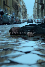 An atmospheric image of a mystery man laying in a cobbled street with a car speeding off, in Rome, Italy.