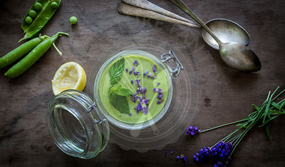Green gazpacho in jar with peas and lavender on wooden background with vintage spoons. Top view