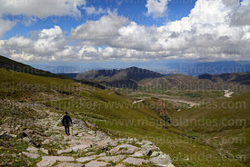 Hiker descending section of Pre-Hispanic Inca Trail towards Calderillas Valley, Cordillera de Sama Biological Reserve, Bolivia