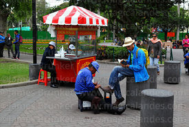 Shoe shiner working in Parque Kennedy, Miraflores, Lima, Peru