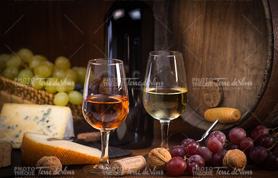 Glasses of rose and white wine cheeses grapesand barrel brown background