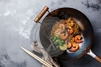 Ramen stir-fry noodles with shrimp in wok pan on gray concrete background copy space