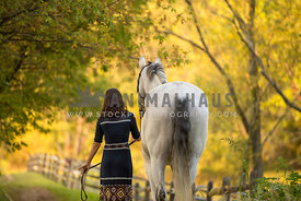 Girl walking horse from back