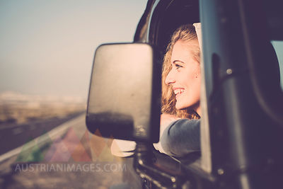 Happy young woman looking out of car window