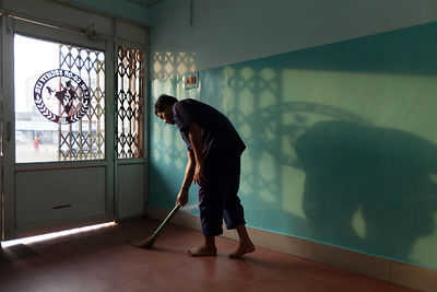 India - Korba - A worker sweeps the floor as early morning light streams through a door throwing a shadow on the wall of the ...