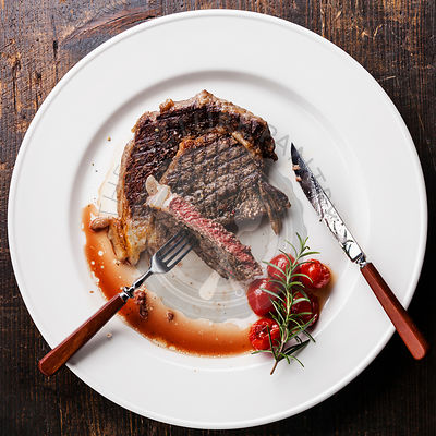 Sliced medium rare grilled Beef steak Ribeye with grilled cherry tomatoes on white plate
