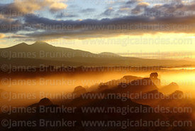 Eroded volcanic rock formations and Cerro San Geronimo volcano at sunrise, Nor Lípez Province, Bolivia