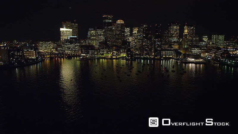 Flying above the harbor toward skyline of Boston's Financial District at night.