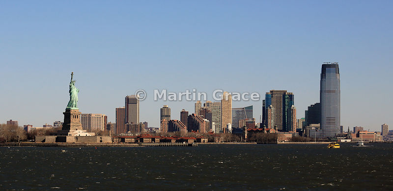 Statue of Liberty (1886) with Jersey City behind, from Staten Island Ferry, New York, USA