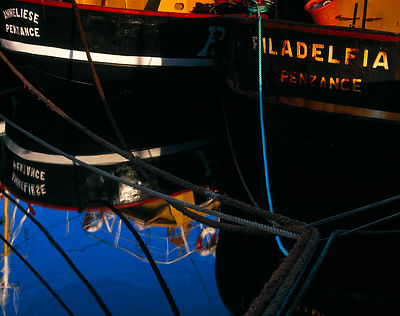 These two trawler sterns, the reflections and mooring lines were photographed just after dawn in the summer. The vibrant blue...