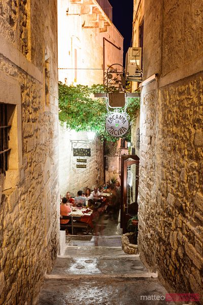 Alley with restaurant in the old town, Vieste, Apulia, Italy