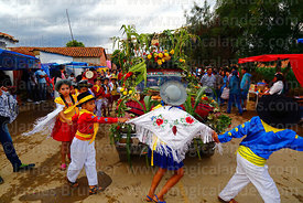 Dancers wearing traditional dress dance around a decorated pick up truck during Carnival parades, San Lorenzo, Tarija Departm...