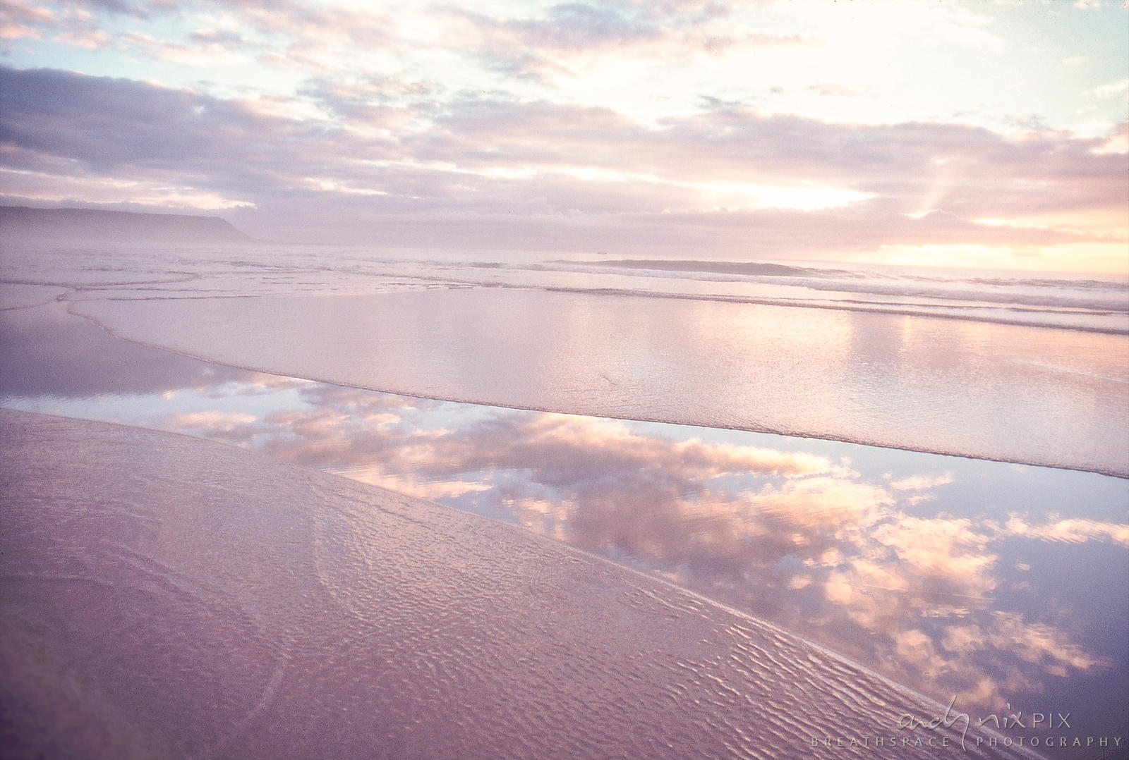 Soft pink sunset clouds reflected in water on the beach.