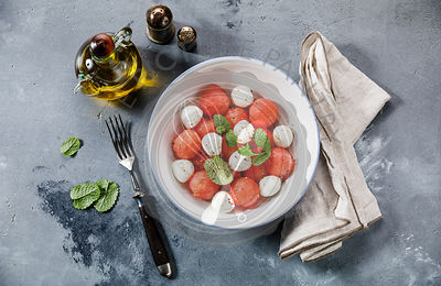 Watermelon salad with mozzarella cheese and mint leaves on gray concrete background