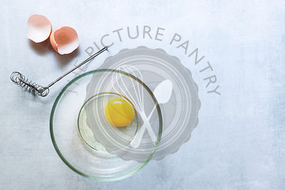 A raw egg in a bowl beside a whisk and eggshell.