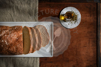 Loaf of rustic, white bread sliced on a white plate with oil and herbs nearby on a rich, wood tabletop with linen.