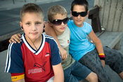 Bosnia - Sarajevo - boys sit on a bench in the street