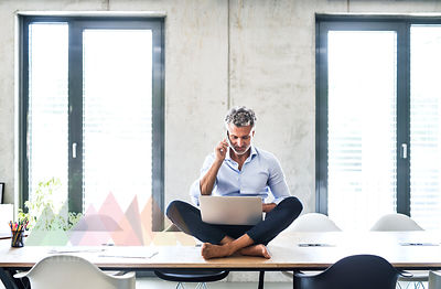Mature businessman sitting barefoot on desk in office using cell phone and laptop