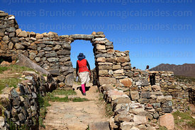 Local girl walking through stone doorway in the Chincana Inca ruins, Sun Island, Lake Titicaca, Bolivia