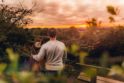 Back view of couple in love in autumnal nature watching sunset