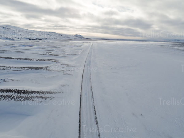 A long icy road leads into the distance in southern Iceland, aerial view