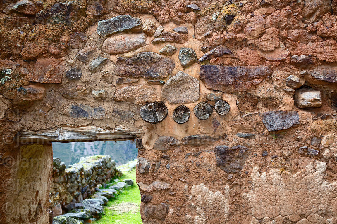 Detail of trapezoid doorway with wooden lintel and beams in wall of  building in Inca site of Pumamarca, Patacancha Valley, C...