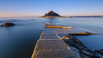 Sunrise on the boat jetty with warm light at St Michael's Mount in Marazion, Cornwall, UK
