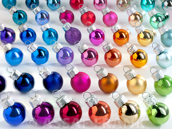 Multi coloured Christmas baubles arranged on white background