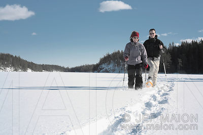 Snowshoeing on frozen lake in forest landscape