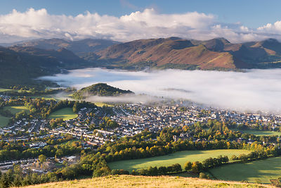 Mist above Derwent Water and Keswick at dawn, Lake District, Cumbria, England, UK. October 2012.