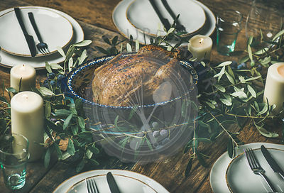Whole roasted chicken with garlic for Christmas eve celebration decorated with olive tree branch over rustic wooden table bac...