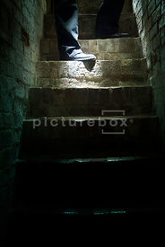 An atmospheric image of a mystery man with a torch descending some dark cellar steps.