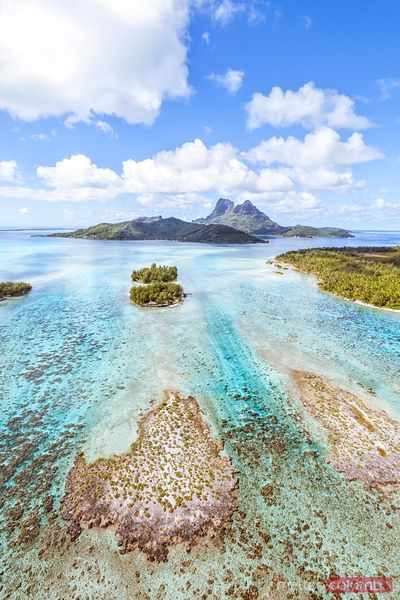 Aerial view of small motus and Bora Bora island, French Polynesia