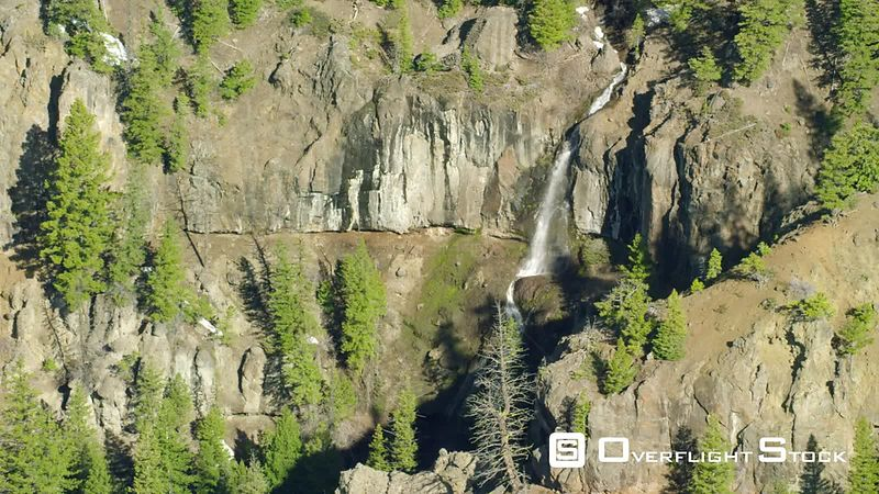 A tall waterfall cascades down steep cliffs within the southern flank of the Absaroka mountain  Range in Yellowstone National...