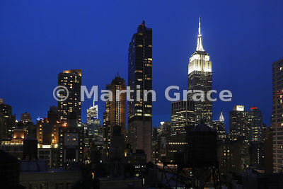 Manhattan skyline at night with illuminated (from left) Bank of America Tower and Empire State Building, with top of Chrysler...