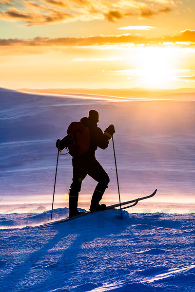 Winter hiker enjoying the sunrise after polar night