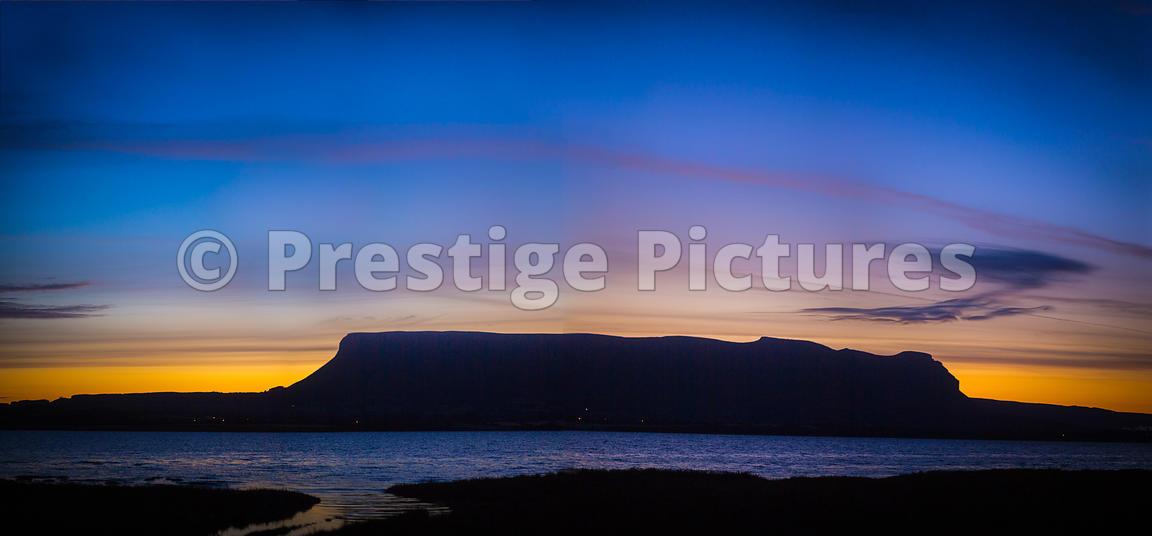 Sunrise with a yellow sky behind the Benbulbin rock