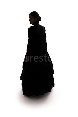 A Victorian woman, in a dress, in silhouette – shot from eye level.