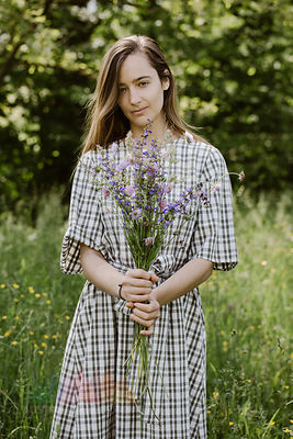 Italy, Veneto, Young woman holding bunch of wild flowers
